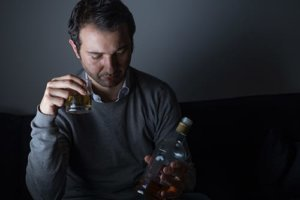 Sad looking man with a bottle shows the answer to is alcohol a depressant?