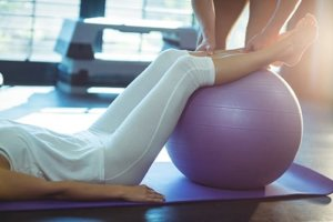 Woman with feet on ball participating in exercise therapy