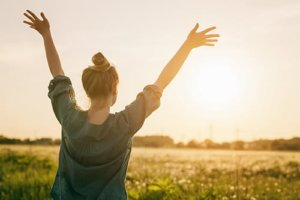 Woman with arms raised during sunset knows the holistic healing definition