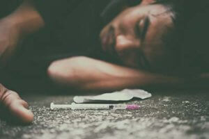 man laying on ground with drugs needing a mens addiction treatment center
